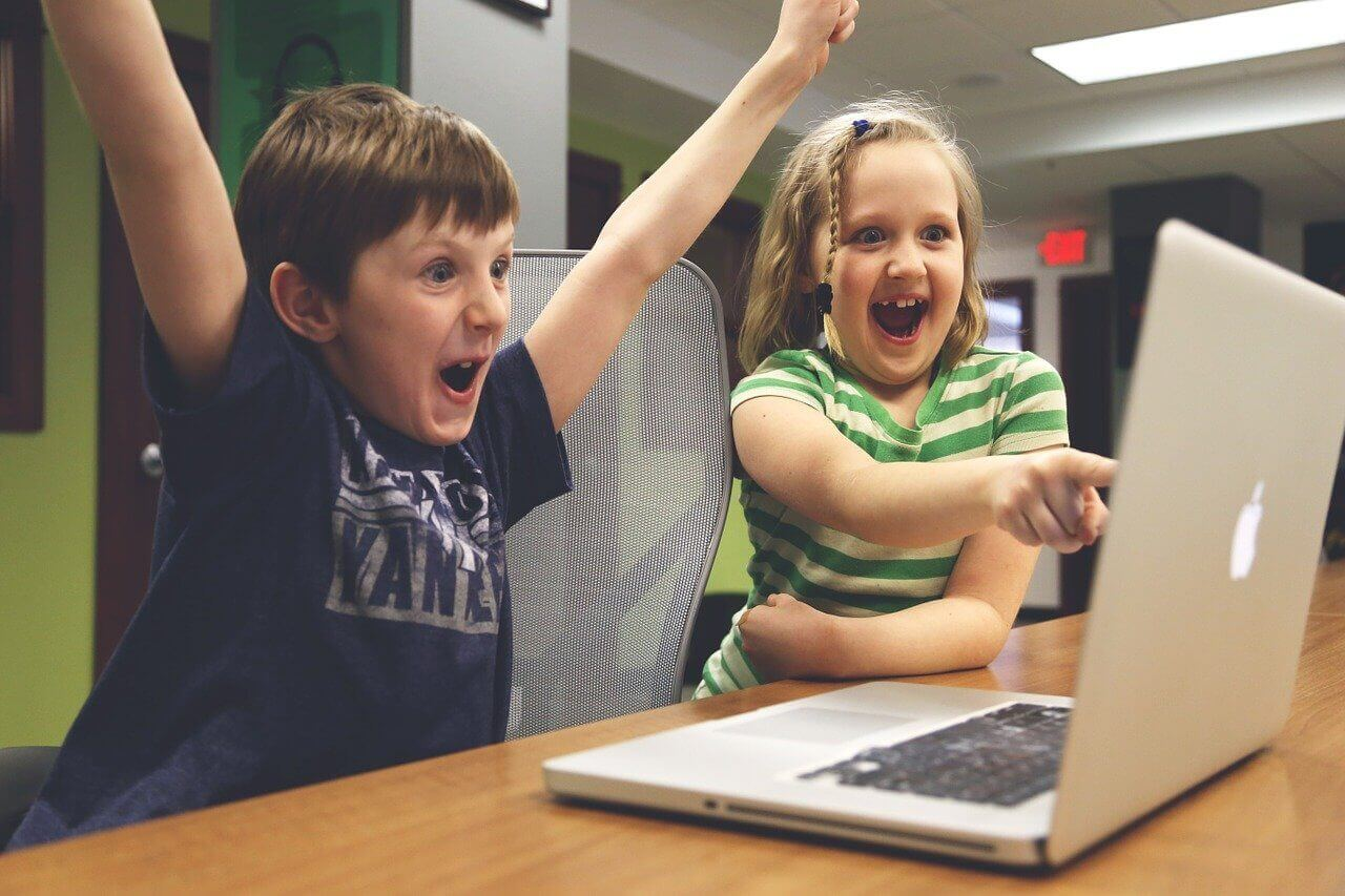 Image of two kids playing video games in front of a computer